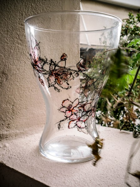 A glass vase hand painted with almond tree flowers, with downcast weather lighting.
