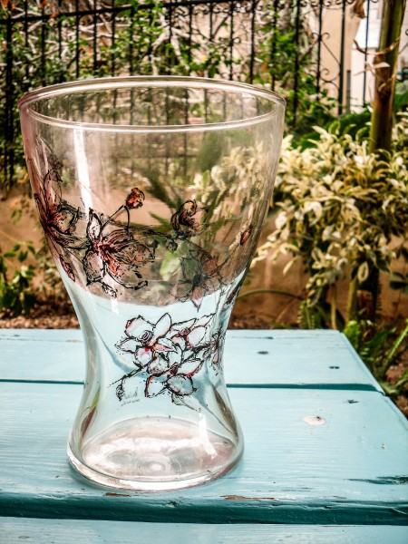 A glass vase hand painted with almond tree flowers, on a blue table.