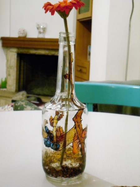 Flower buds inspired painted glass bottle as a centerpiece, close up.